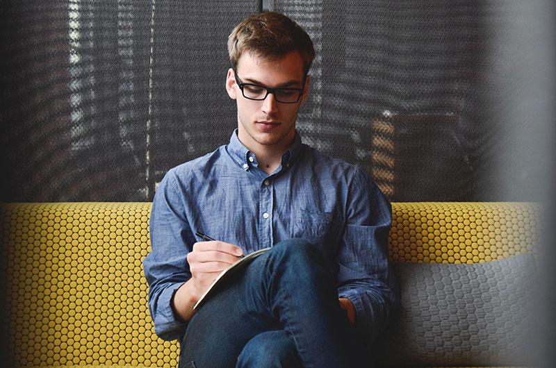 Chico con gafas, escribiendo con estilográfica